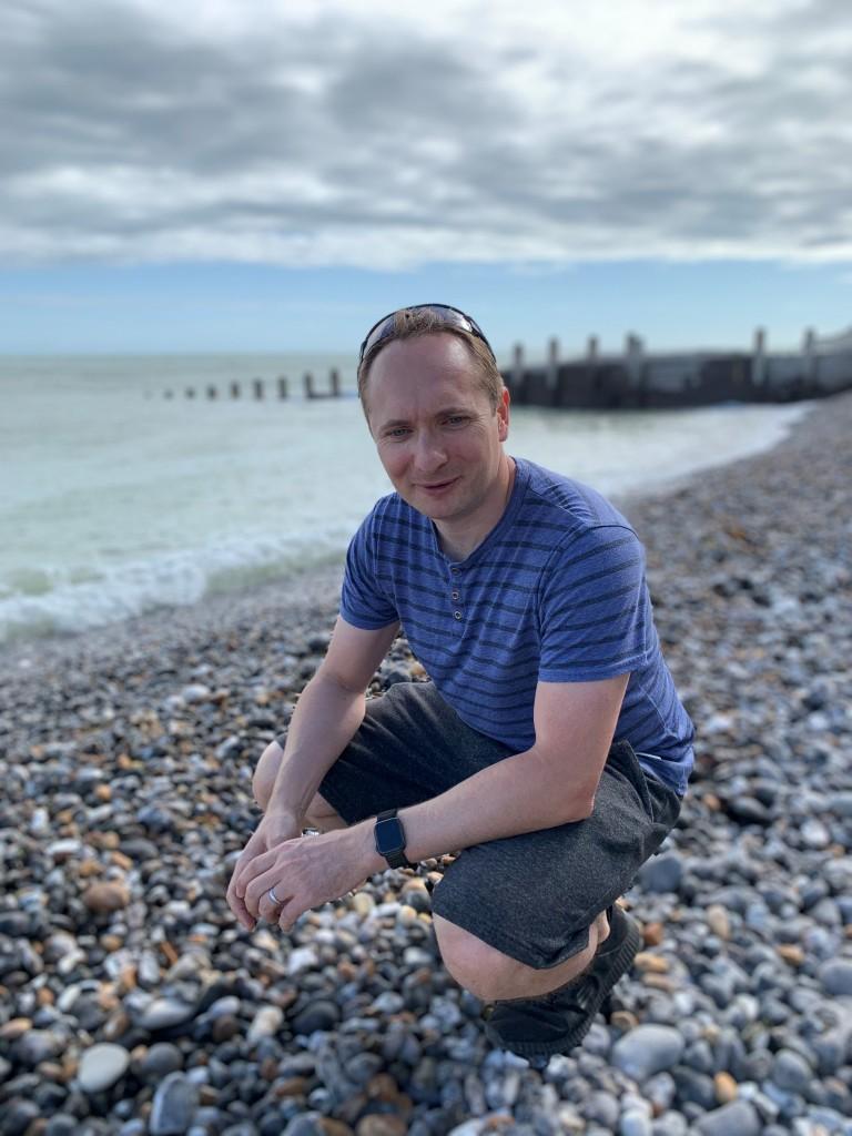 Paul Smyth, crouching on a beach